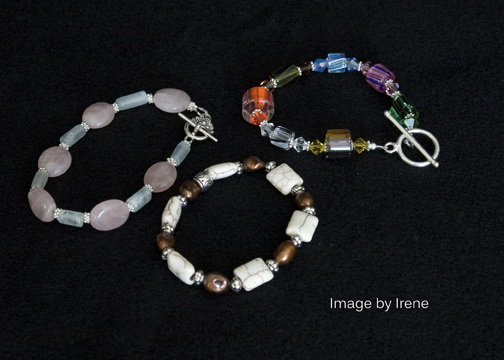 "Left to Right - Rose quartz and aquamarine with base metal clasp, 8"" - $30. White jasper and pearl stretch bracelet - $15. Cane beads and crystals with base metal clasp, 8"" - $30"