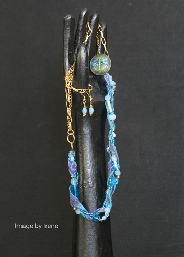 "Blue glass beads, silk ribbon, and firefly button on base metal chain, 28"" with matching bead earrings on gold plated ear wires."
