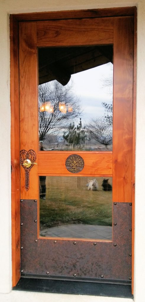 Custom carved exterior door featuring glass panels, Celtic knot horse heads with the Tree of Life and finished with antique copper plating and Clovis rivets.