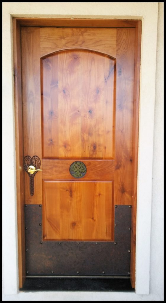 Custom carved exterior door featuring Celtic knot horse heads with the Tree of Life and finished with antique copper plating and Clovis rivets.