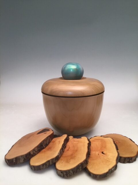 """""""Coaster Cave #1"""" ~8X8X10. This lathe-turned and hollowed lidded container Hides a set of 5 (or 6, or 8 if you wish) maple, bark-on Coasters. The Sugar Maple 'jar' is painted in transparent gold to Show the grain and an opaque iridescent electric blue knob to Lift the lid. All are over-coated with polycoat buffed to a satin Sheen that is durable, washable, functional. Signed by jsbarany@aol.com 5099495873. $180"""