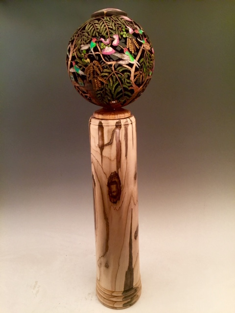 """""""Hummingbird Heaven"""" In October when this tree blooms, the hummingbirds come from Afar to buzz, sip, cavort, and duel with eachother for blossom Rights. The pink flowers sit for three weeks, beckoning the tiny Birds before the Fall migration is brought on by cold November Weather. ~26X8X4"""", a carved lidded vase. The dome and the vase are Carpathian Walnut. Painted in acrylics, clear coated with Polycoat for easy cleaning. Signed by jsbarany jsbarany@aol.com 5099495873 NFS (Private collection) Ps. Can anyone remember the name of this tree that Has massive pink blossoms in the fall?"""